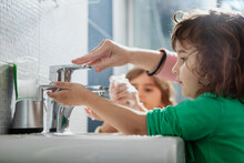 Mother With Her Kids Washing Hands In The Bathroom