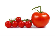 Trusses Of Small Cherry Tomatoes Next To Big Salad Tomatoe Fruit Isolated On White Background
