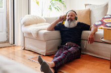 Mature Man Listening To Music With A Beer