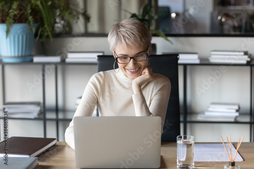 Smiling young Caucasian businesswoman in glasses sit at desk look at laptop screen working online. Happy 30s woman in eyewear busy using computer in office, consult client or customer on internet. - 384869834