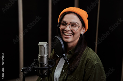 Fototapeta Portrait of cheerful young woman, hip hop artist singing into a condenser microp
