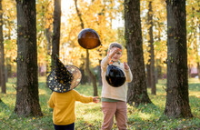 Black Balloons, A Witch's Hat, Children Playing, Running Through The Forest. Halloween Holiday.