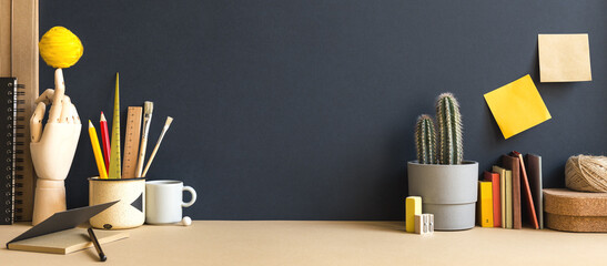 Creative desk with notebook, desk objects, office supplies, books, and cactus on a dark blue background.
