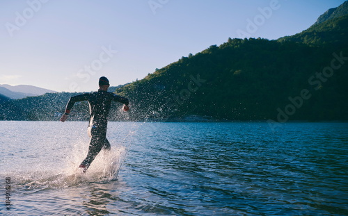 Photographie triathlon athlete starting swimming training on lake
