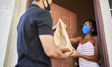 Food Delivery In The Covid-19 Era, African American Woman Opening Door To Receive Take Out Order While Wearing Mask