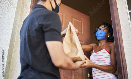 food delivery in the covid-19 era, african american woman opening door to receive take out order while wearing mask © Joshua Resnick