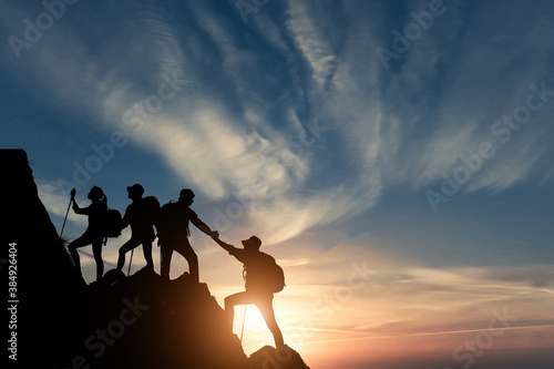 Fotografering Silhouette male hiker groups celebrating success on top of a mountain in a majestic sunset and Two climber helping to hike up