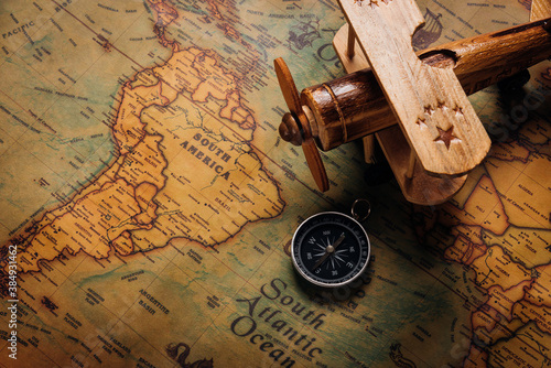 Photographie Old compass discovery and wooden plane on vintage paper antique world map backgr