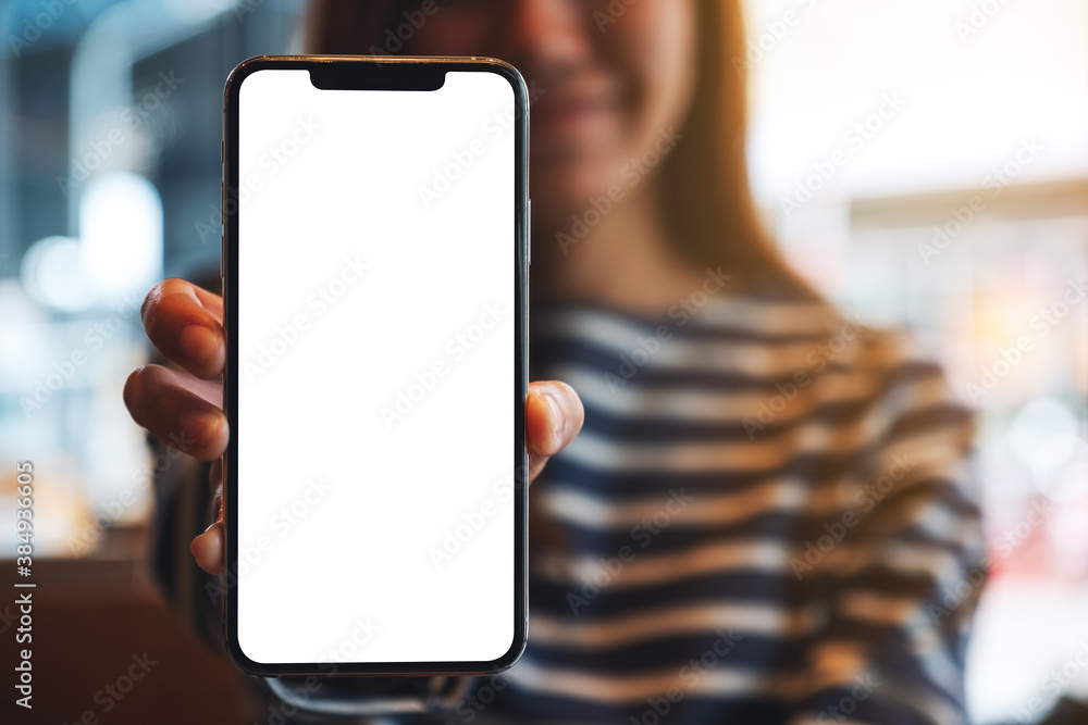 Fototapeta Mockup image of a beautiful asian woman holding and showing a mobile phone with blank white screen
