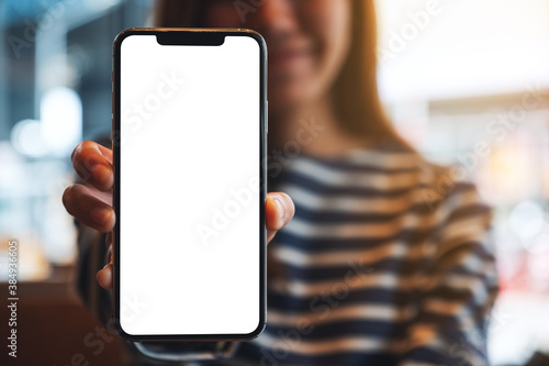 Mockup image of a beautiful asian woman holding and showing a mobile phone with Fototapeta