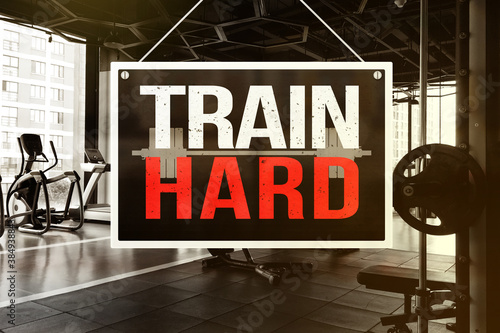 A signage with words - Train Hard - in front of a gym or fitness center Tapéta, Fotótapéta