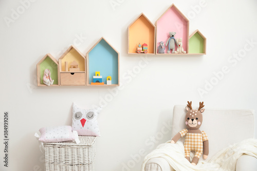 Obraz Stylish baby room interior design with house shaped shelves and comfortable armchair - fototapety do salonu