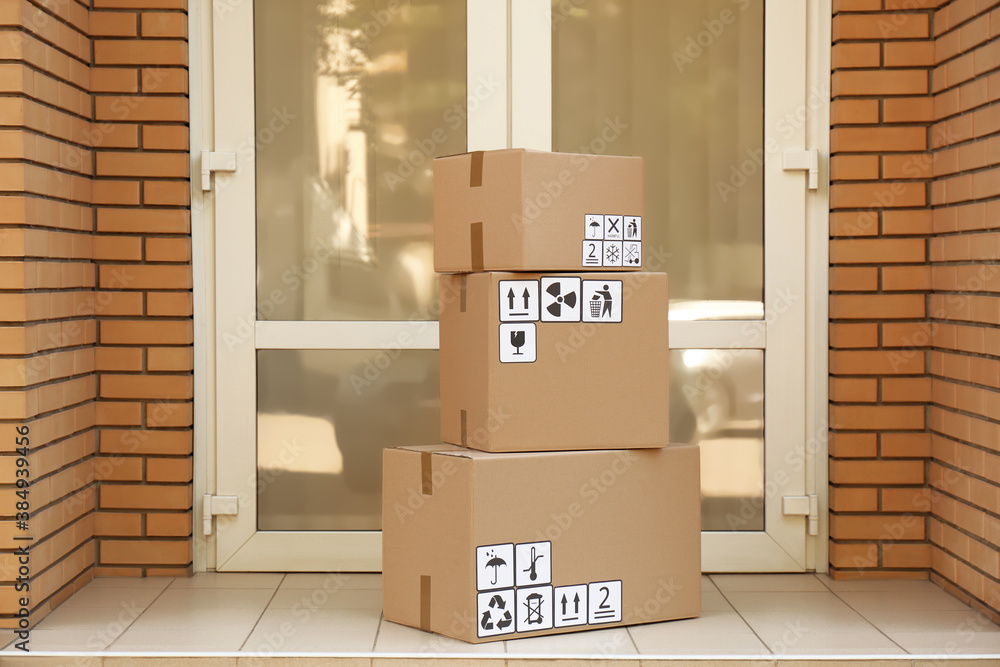 Fototapeta Cardboard boxes with different packaging symbols on floor near entrance. Parcel delivery