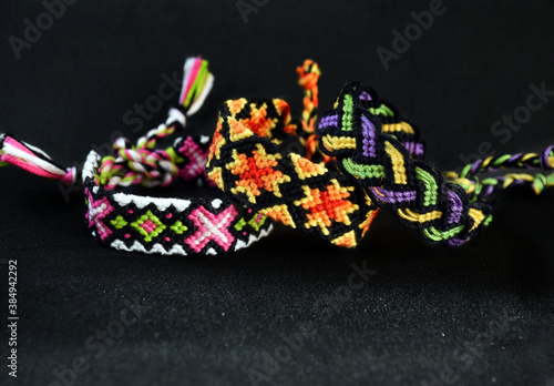 Slika na platnu Selective focus of 3 woven DIY friendship bracelets handmade of embroidery bright thread with knots on black background