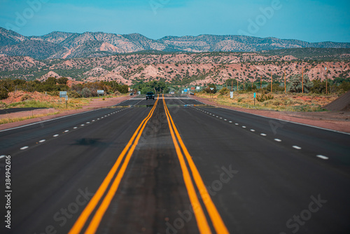 Fotografie, Obraz Panorama view of an endless straight road running through the barren scenery of the American Southwest