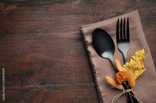 Fototapeta Seasonal table setting on wooden background, space for text. Cutlery with autumn decorations, top view obraz