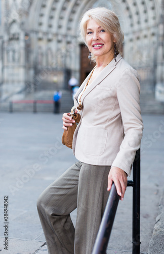 Obraz Adult woman 50s years old is walking in classic dress in old city. - fototapety do salonu