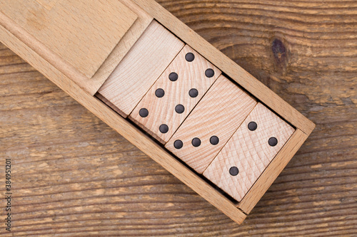 Drewniane klocki domina w pudełku.