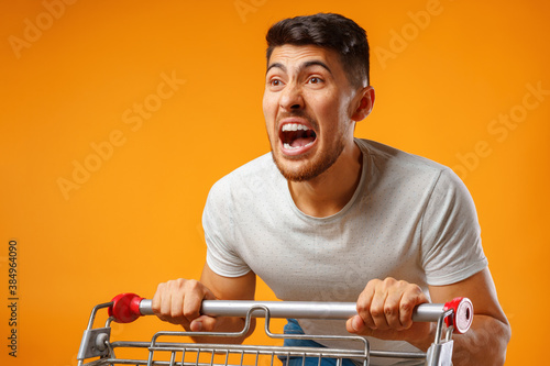 Funny crazy man rushing with shopping trolley to sale Wallpaper Mural
