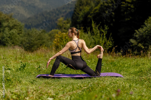 Fitness woman sitting in a yoga pose in a park Fototapet