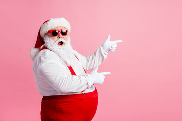Profile side photo of astonished santa claus point index finger copyspace x-mas ads wear sunglass headwear suspenders headwear isolated over pastel color background