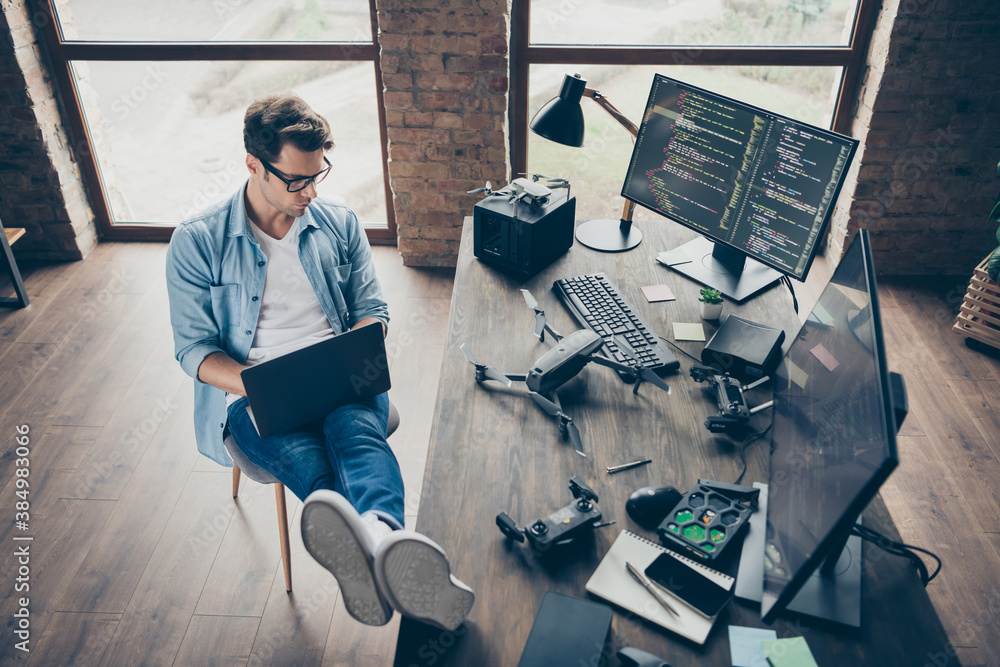 Fototapeta Above high angle view of his he nice attractive focused guy geek expert working remotely typing coding calculating game development dev at modern industrial home office work place station