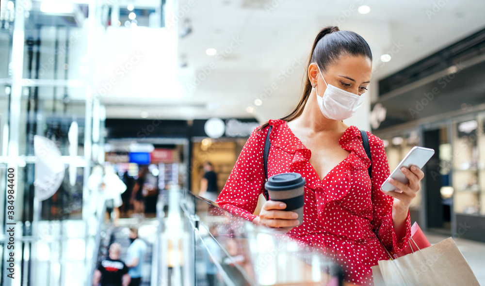 Fototapeta Woman with face mask standing and using smartphone indoors in shopping center, coronavirus concept.