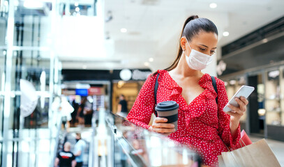 Woman with face mask standing and using smartphone indoors in shopping center, coronavirus concept.