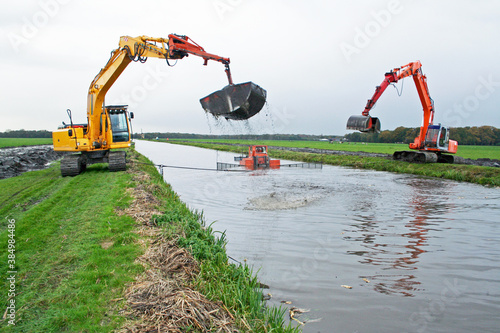 Fotografering Dreding of an inland canal by two cranes; a silt pusher boat pushes the sediment towards the crane; sediment is dispursed on land