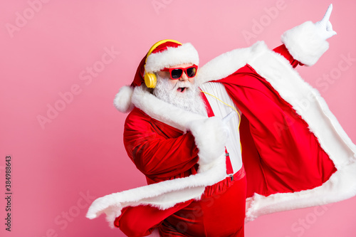 Photo crazy funky cool bearded santa claus enjoy listen headphone stereo x-mas christmas music dance raise finger wear sunglass headwear suspenders isolated pastel color background