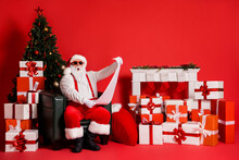 Portrait Of His He Attractive Funky Fat Amazed Stunned Santa Sitting In Armchair Living-room Reading Long Paper Letter Giftbox Pile Stack Isolated Bright Vivid Shine Vibrant Red Color Background