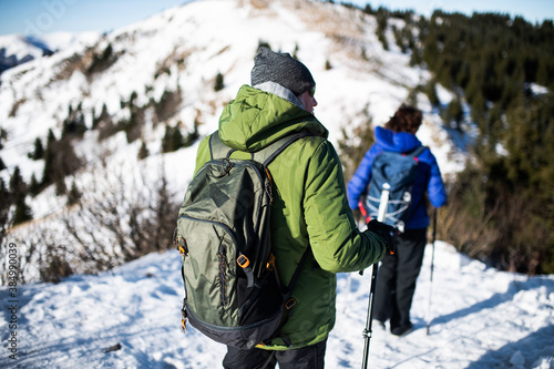 Fototapeta Rear view of senior couple hikers in snow-covered winter nature, walking. obraz