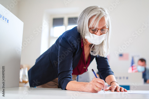 Obraz Portrait of woman voter with face mask in polling place, elections and coronavirus concept. - fototapety do salonu