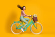 canvas print picture Full length body size side profile photo of cheerful girl riding blue bicycle with basket of flowers isolated on vibrant yellow color background
