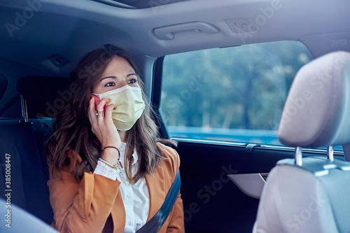Caucasian woman with a face mask wearing her cell phone in a car - Business woma Tableau sur Toile