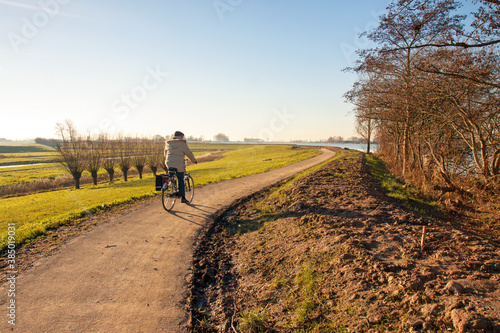 Cuadros en Lienzo Man on a bicycle drives on a recently raised dike in a Dutch polder landscape