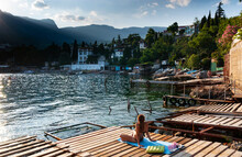 A Woman Sunbathes On A Wooden ...