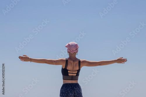 Obraz Mujer con pañuelo rosa de cancer de mama con los brazos abiertos de espalda - fototapety do salonu