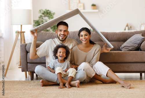Fototapeta Happy family under fake roof in living room.