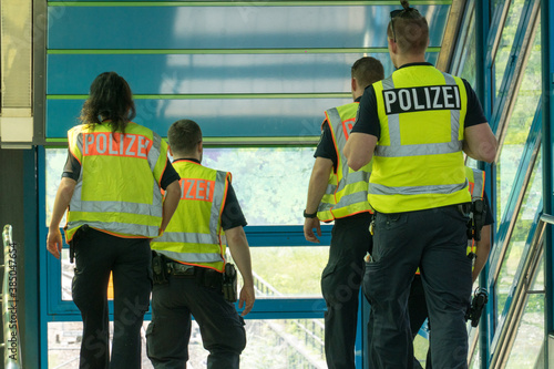 Fototapeta Berlin, Germany - June 13, 2019: Back turned policewoman and policemen going dow