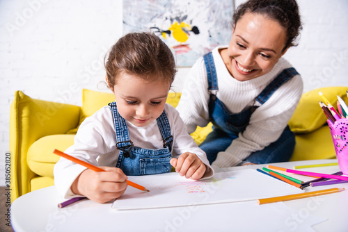 Obraz Daughter drawing with color pencils near mother at home - fototapety do salonu