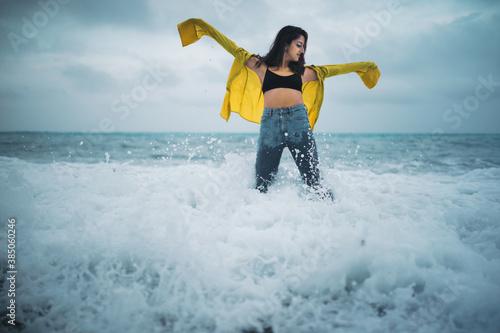 Fotomural ragazza con maglia gialla e jeans si fa il bagno a mare in inverno