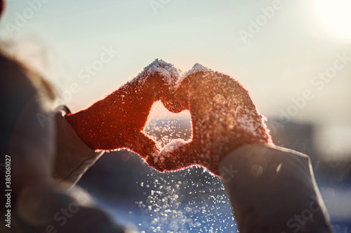 Obraz Heart shape symbol of the women's mittens in winter frosty sunset. Concept of frosty winter, dating, valentines day and love. - fototapety do salonu