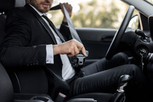 Unrecognizable Man In Suit Fasten Seat Belt In His Car