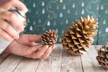 Woman Painting Golden Pinecones For Christmas