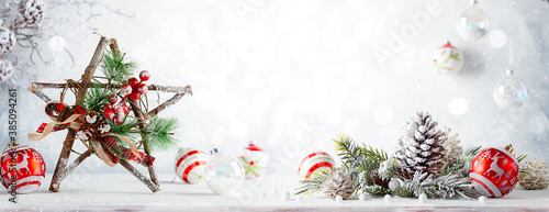 Christmas still life with decorated wooden Christmas Star on light background. Winter festive concept.