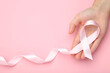 Breast cancer concept. Female hand holding pink ribbon
