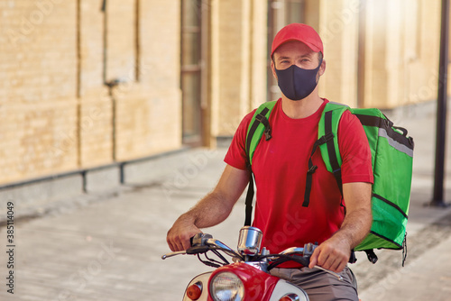 Fototapeta Young caucasian male courier wearing protective face mask obraz