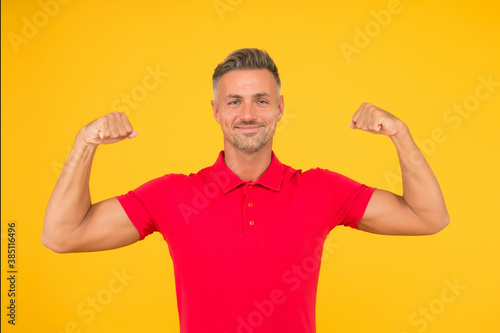 Foto Strong athletic guy smile in red tshirt flexing muscular arms yellow background,