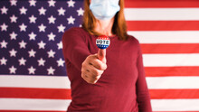 Woman With Vote Sticker On Thumbs Up Finger And Face Mask At 2020 American Elections.